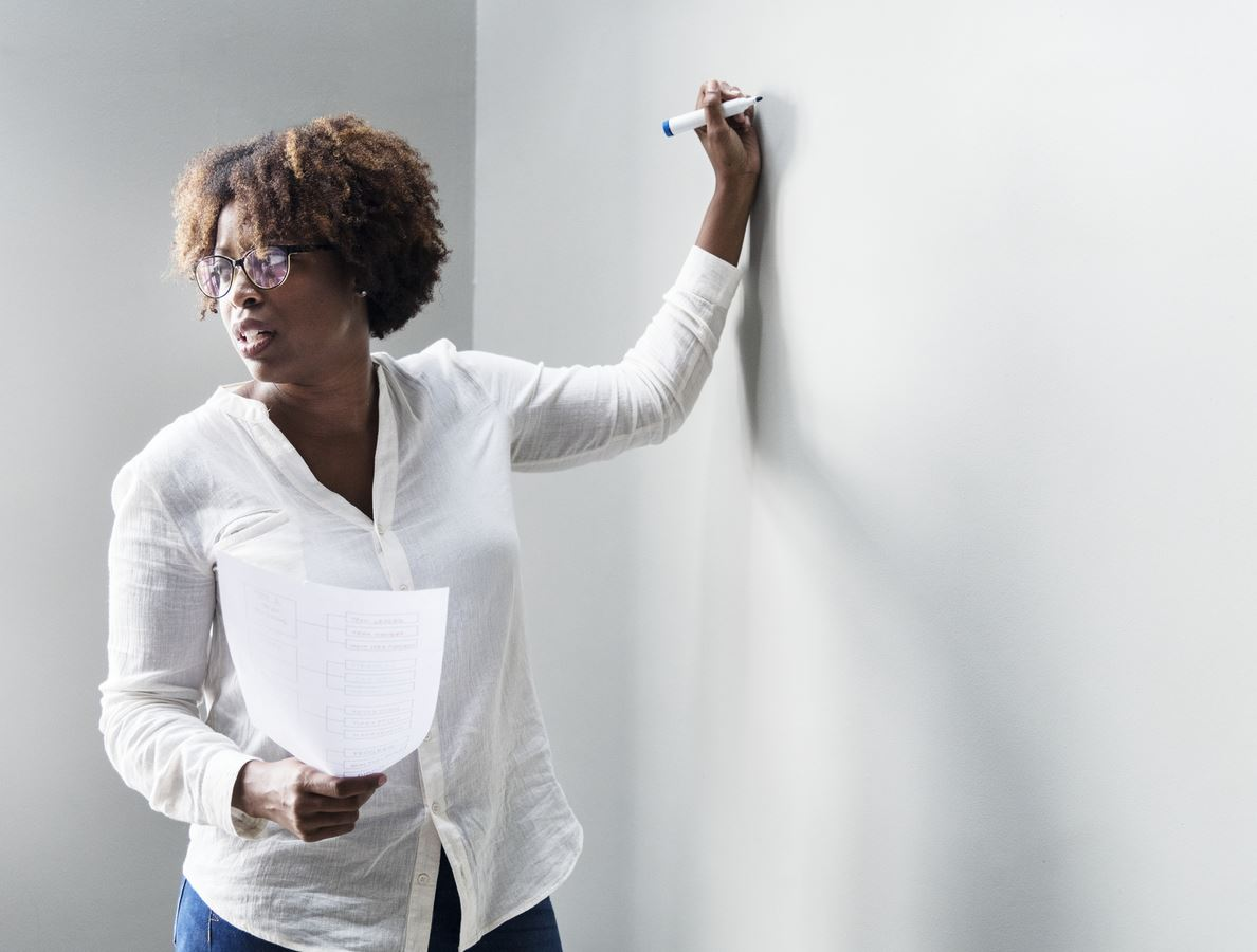 Picture of Black female teacher writing on a white board