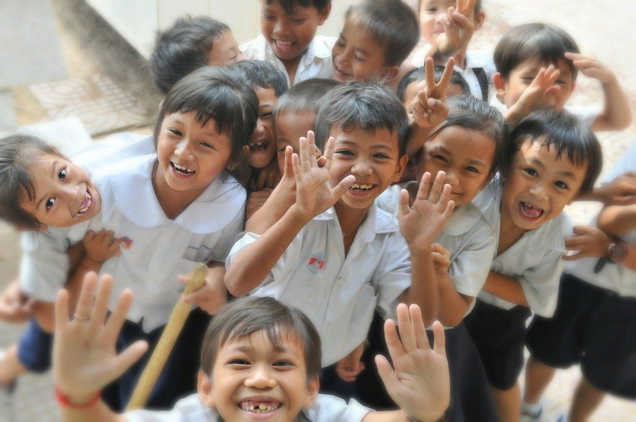 Asian school children smiling and waving at the camera