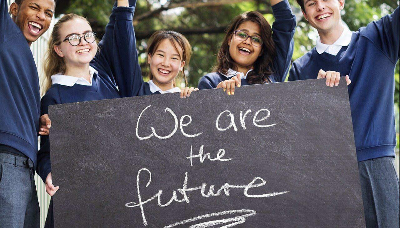 "Five middle or high school students of mixed race, smiling and holding a sign that says ""we are the future"""